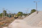 Wyładunek ziemi z wagonów oczyszczarki -- Na pierwszym planie hałda nowego tłucznia kolejowego. W oddali skład wagonów samowyładowczych z taśmociągiem. Ziemia wydobyta przez oczyszczarkę torową jest wyładowywana na niskiej rampie.