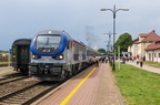 SU160-006 -- Lokomotywa spalinowa PKP Intercity ze składem TLK Mamry rel. Gdynia Gł. - Białystok na stacji Giżycko. Na torze obok stoi pociąg turystyczny z parowozem.